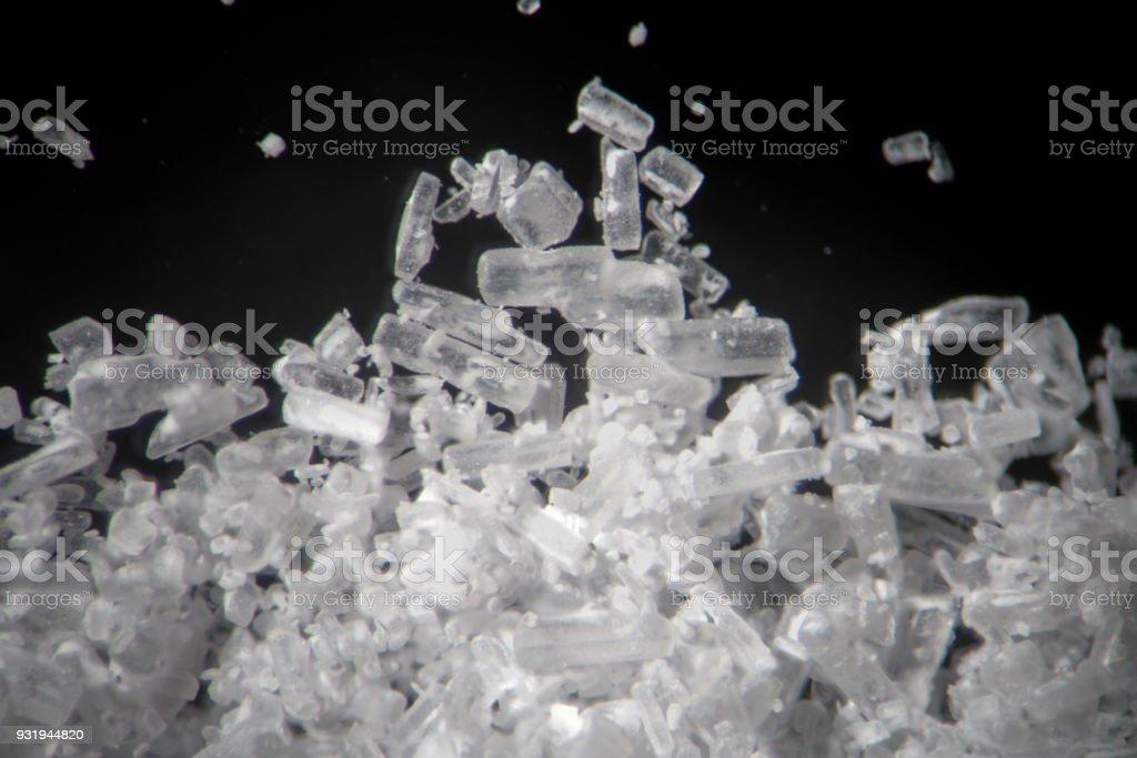 Creatine crystals by microscope looks like methamphetamine. Athletic dietary supplement in details supermacro close-up. White cristales on black background or low key stock photo