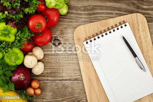 Directly above view of notebook and cutting board with raw vegetables around it