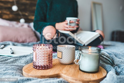 Cropped shot of an unrecognizable young woman relaxing with a book and a cup of coffee on her bed at home