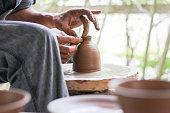 A man creates a small vase on a pottery wheel