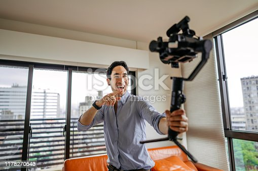 Joyful vlogger filming vlog on the move at apartment, holding professional camera
