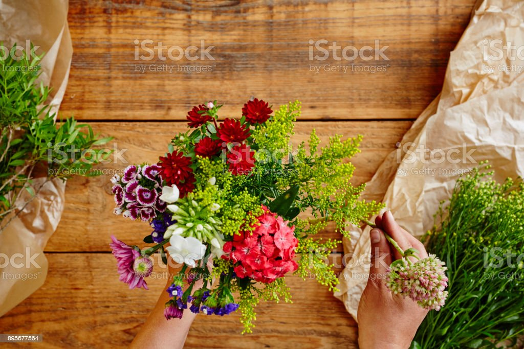 creating a wild flowers bouquet flowershop with hands stock photo