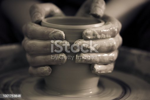 Creating ceramic products of white clay close-up. The sculptor in workshop makes clay jug closeup. Master crock. Twisted potter's wheel. Art, creativity. Cultural traditions. Handmade. Craft.