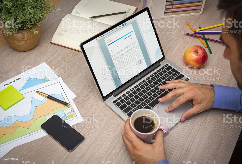 Creating invoice on laptop stock photo