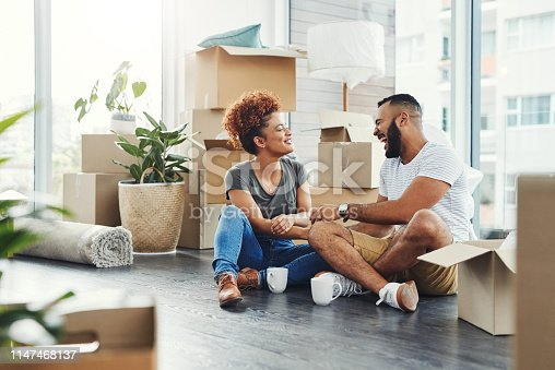 Shot of a young couple taking a break while moving house