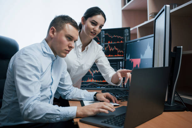 Creating new project. Team of stockbrokers are having a conversation in a office with multiple display screens stock photo