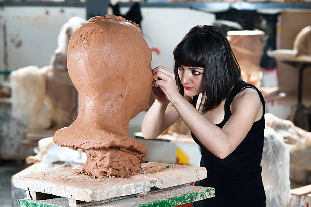 Creating Sculpture Beautiful young sculptor creates a clay sculptureTo see my other photos please click here: fine art statue stock pictures, royalty-free photos & images
