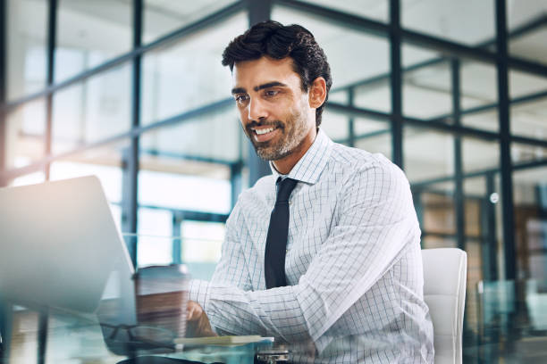 Creating success. How the expert does it Shot of a businessman working on a laptop in his office spanish and portuguese ethnicity stock pictures, royalty-free photos & images
