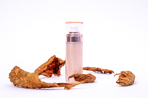 istock Creative advertising of cosmetic product for autumn skincare containing natural ingredients in beautiful bottle with dispenser on white background, dry tree leaves around for decoration, copy space 1271601223