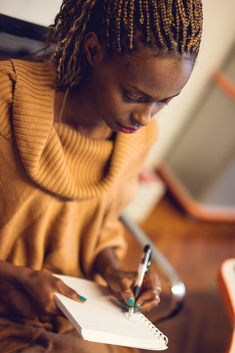 Young African American female writer taking notes of her ideas.
