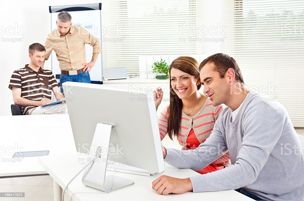 Creative Agency Four people working in two groups in an office. Smiling couple on the foreground watching a new project on the monitor. Adult Stock Photo