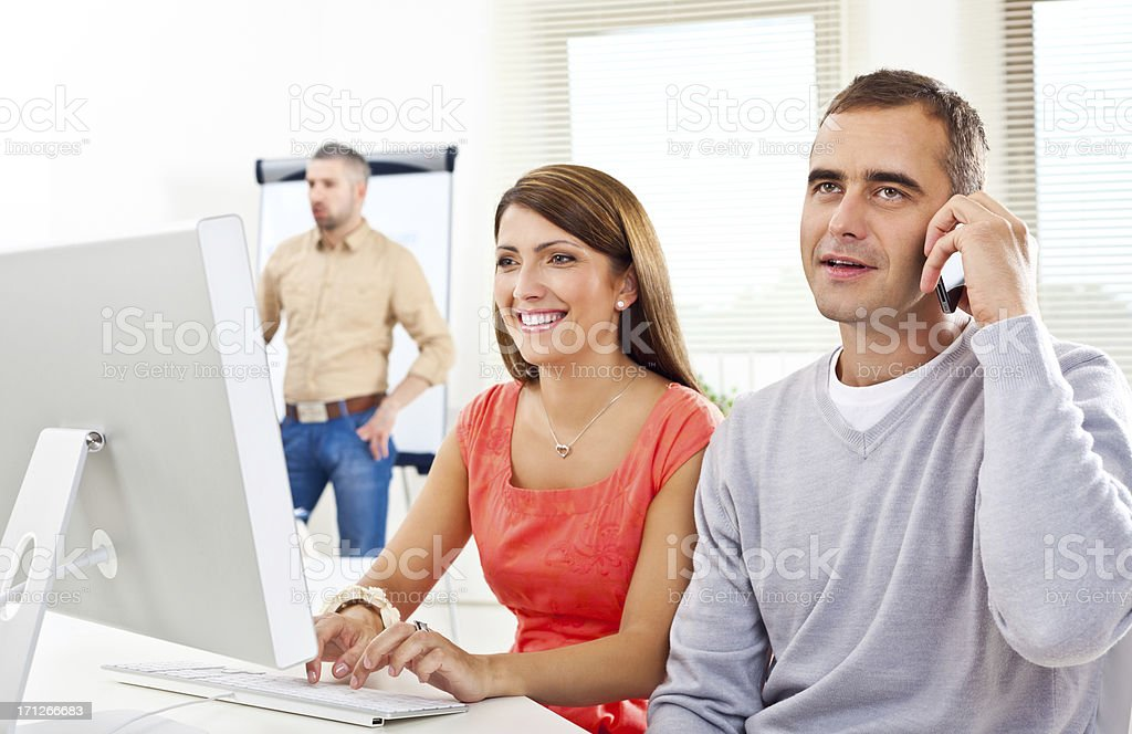Creative agency Smiling woman typing on computer keyboard and her colleague talking on the phone. Adult Stock Photo