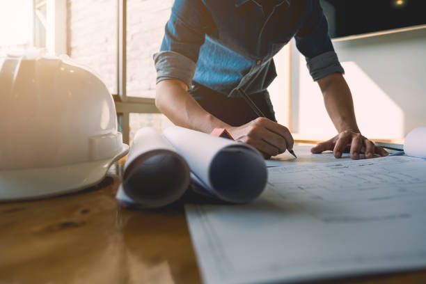 Creative architect projecting on the big drawings in the dark loft office or cafe with dark and retro style stock photo