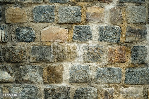 creative art background from an old wall with stonework in a row of multi-colored rectangular granite blocks and cement mortar. side view