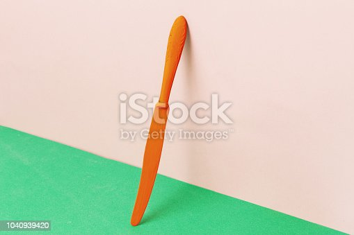 istock Creative art background. Orange knife, on pink background and green table 1040939420