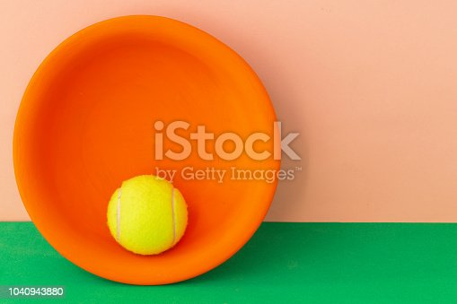 istock Creative art background. Tennis ball in an orange plate on pink background and green table. Copy space 1040943880