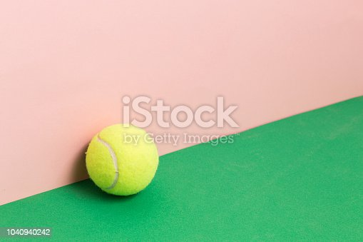 istock Creative art background. Tennis ball, on pink background and green table 1040940242