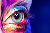 Closeup image of woman eye with creative makeup painted different colors
