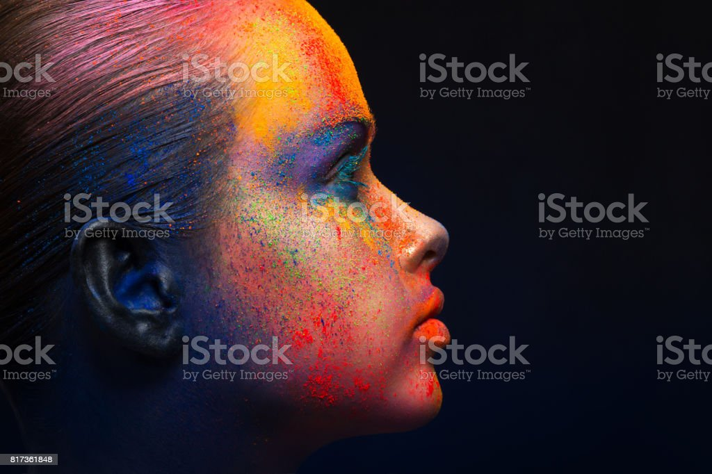 Holi festival of colors background. Female face art with creative...