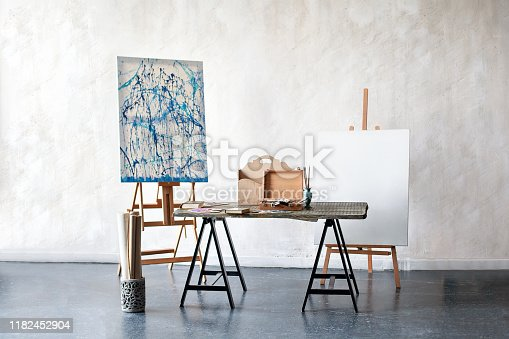 Creative artist workplace no people hobbies. Painting Studio of a freelance artist. Easel, canvas, brushes, pencils, paints with albums on the table. The interior in the studio of the artist, workshop