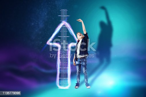 istock Creative background, Boy on a blue background shows how he grew up, dreams of becoming an adult. The concept of big growth, business, maturity, active growth. 1135779395