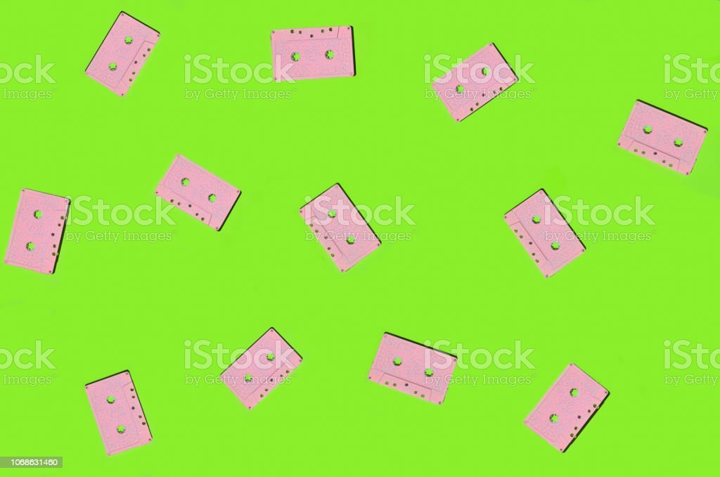 Creative background from pink audio cassettes on a green surface. Top view. – zdjęcie