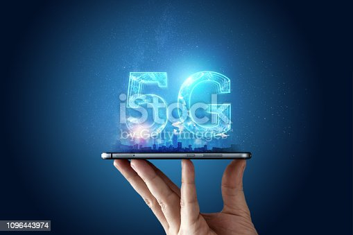 istock Creative background, male hand holding a phone with a 5G hologram on the background of the city. The concept of 5G network, high-speed mobile Internet, new generation networks. Copy space, Mixed media. 1096443974