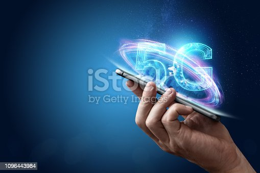istock Creative background, male hand holding a phone with a 5G hologram on the background of the city. The concept of 5G network, high-speed mobile Internet, new generation networks. Copy space, Mixed media. 1096443984