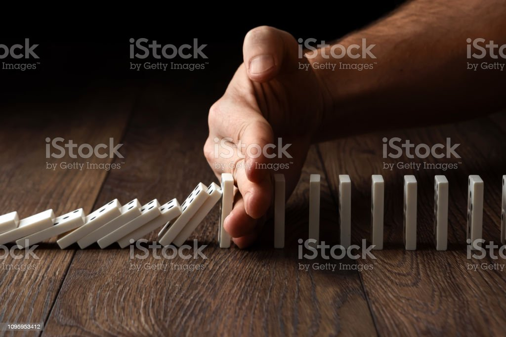 Creative background, Men\'s hand stopped domino effect, on a brown...