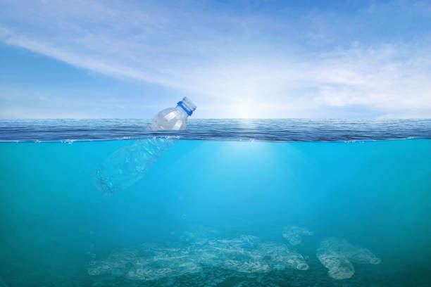 Creative background, plastic bottle floating in the ocean, a bottle in the water. stock photo