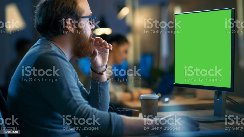 Creative Bearded Man Works on a Personal Computer with Isolated Mock-up Green Screen. His Office Space is Modern and Cool. stock photo