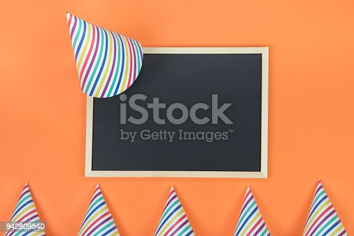 1093222958istockphoto Creative birthday party decoration on orange background. Top view with frame and space for text. 942809540