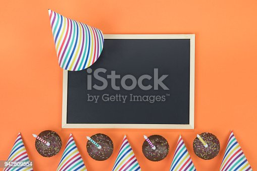 1093222958 istock photo Creative birthday party decoration on orange background. Top view with frame and space for text. 942809554