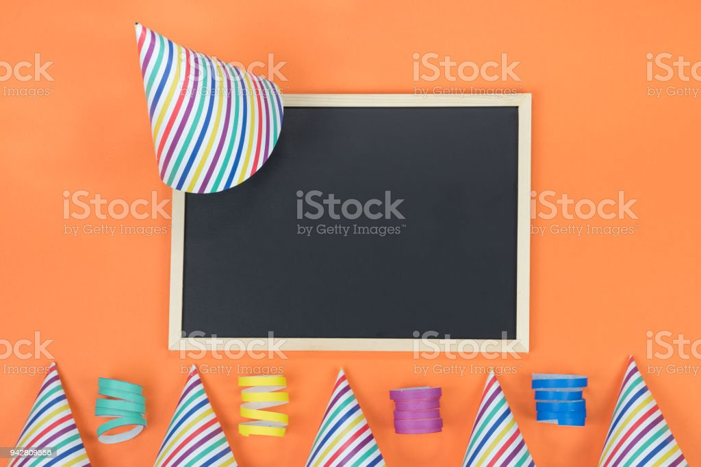 Creative birthday party decoration on orange background. Top view with frame and space for text. stock photo