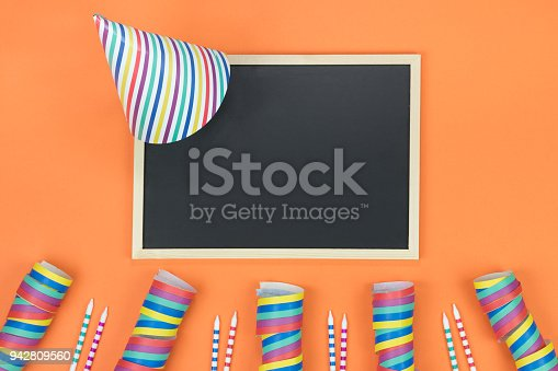 1093222958 istock photo Creative birthday party decoration on orange background. Top view with frame and space for text. 942809560