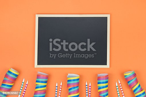 1093222958 istock photo Creative birthday party decoration on orange background. Top view with frame and space for text. 942809562