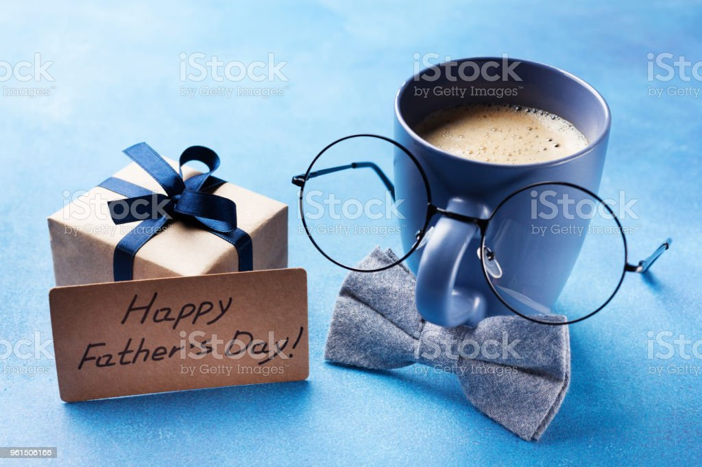 Creative breakfast on Happy Fathers Day with gift box, funny face from cup of coffee, eyeglasses and bowtie. stock photo