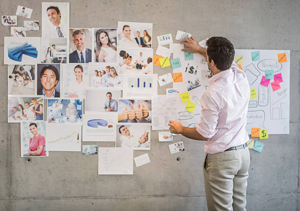 Creative business man creating a wall chart Creative business man in his 20s creating a wall chart at the office market research stock pictures, royalty-free photos & images