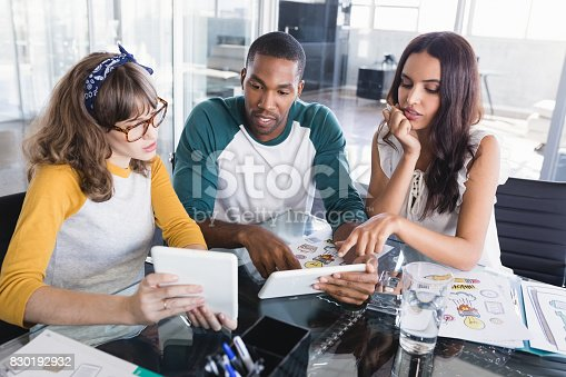 557608497istockphoto Creative business people discussing over digital tablets at office 830192932