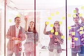 Confident colleagues sticking notes on glass wall in office