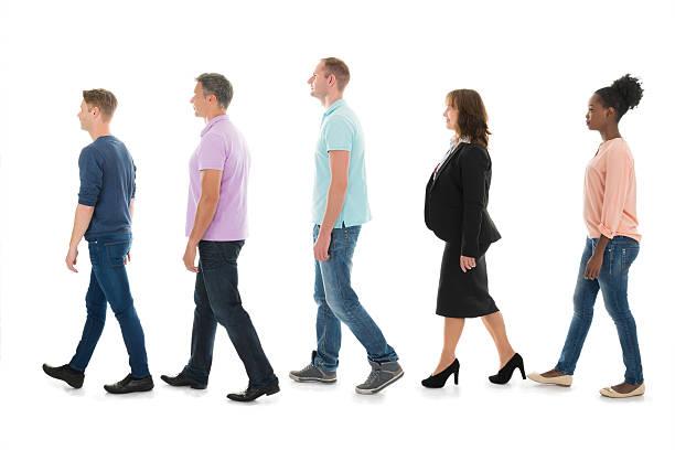 creative business people walking with manager in row - schwarze schlange stock-fotos und bilder