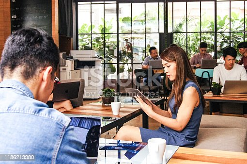 937328186 istock photo Creative business people working independently in open space 1186213380
