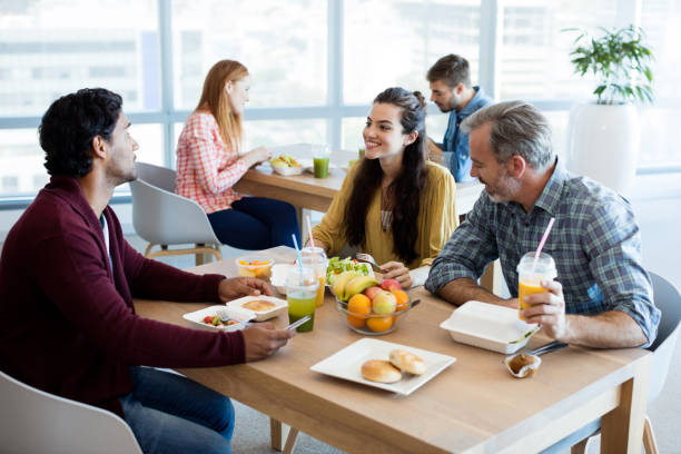 Creative business team discussing while having meal stock photo