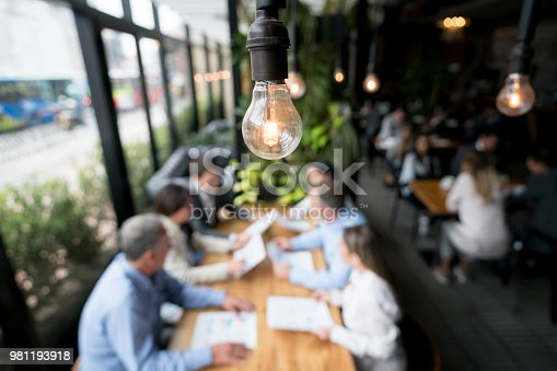 Creative business team in a meeting at a restaurant - focus on a lightbulb