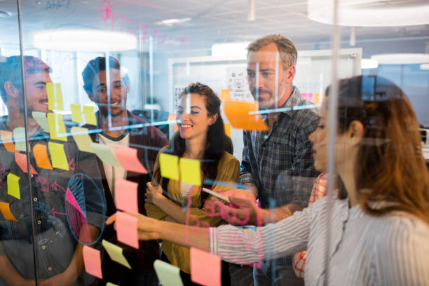 creative business team looking at sticky notes on glass window - post it notes стоковые фото и изображения
