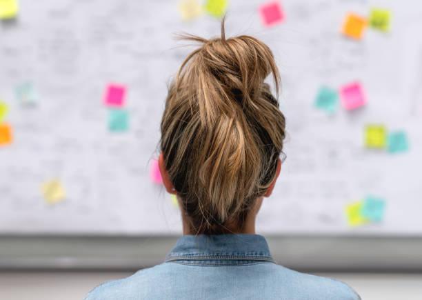 mujer de negocios creativo lluvia de ideas en la oficina usando una pizarra - design thinking fotografías e imágenes de stock