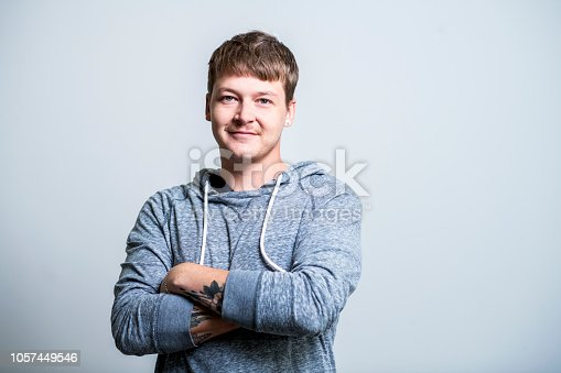 Portrait of confident creative businessman against gray background. Male entrepreneur is standing with arms crossed. He is wearing smart casuals.