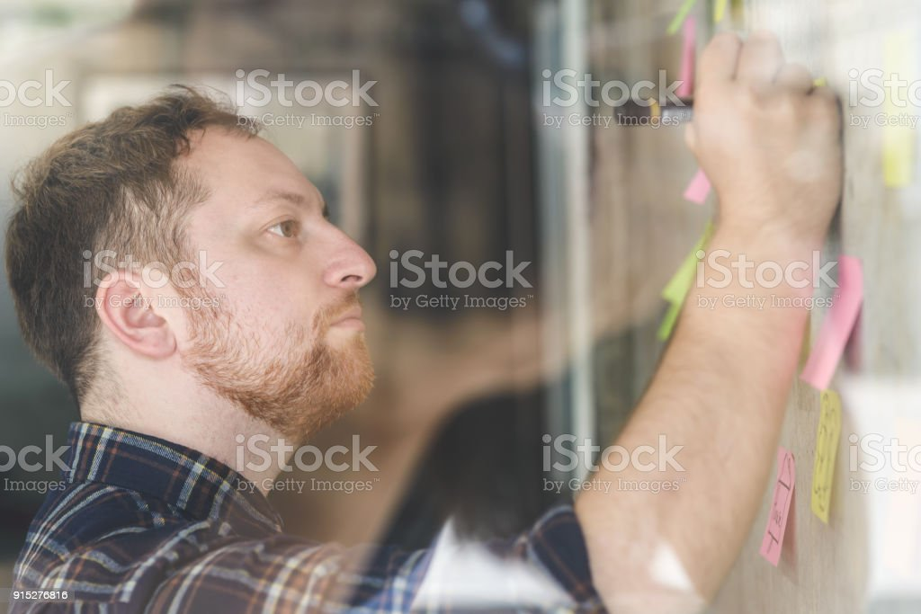 Creative businessman writing notes on paper in office stock photo