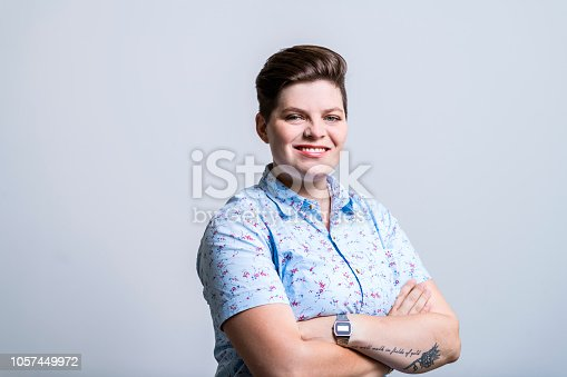 Portrait of confident creative businesswoman and entrepreneur against gray background. Female entrepreneur is smiling while standing with arms crossed. She is wearing patterned shirt.