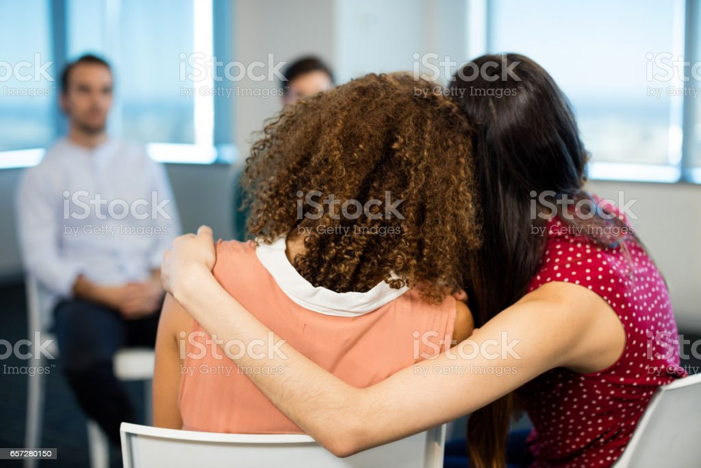 Creative businesswoman embracing each other at office stock photo